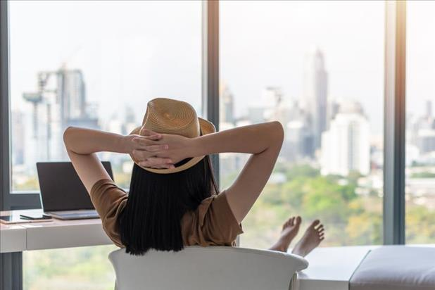 Woman with hat and bare feet relaxing in office chair while looking out window