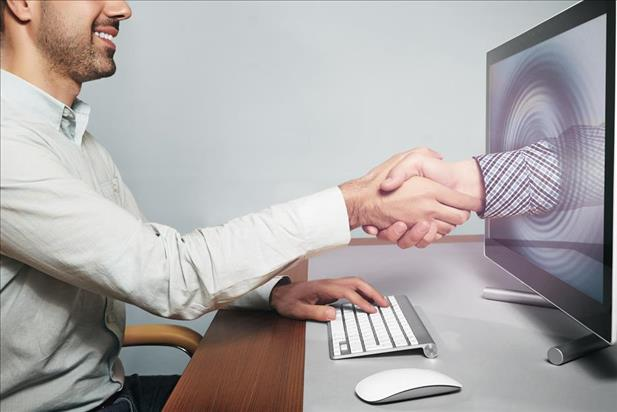 virtual onboarding/virtual handshake image concept with new hire shaking hands with his new manager through a computer screen