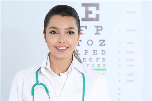 Young female optometrist posing in front of eye chart