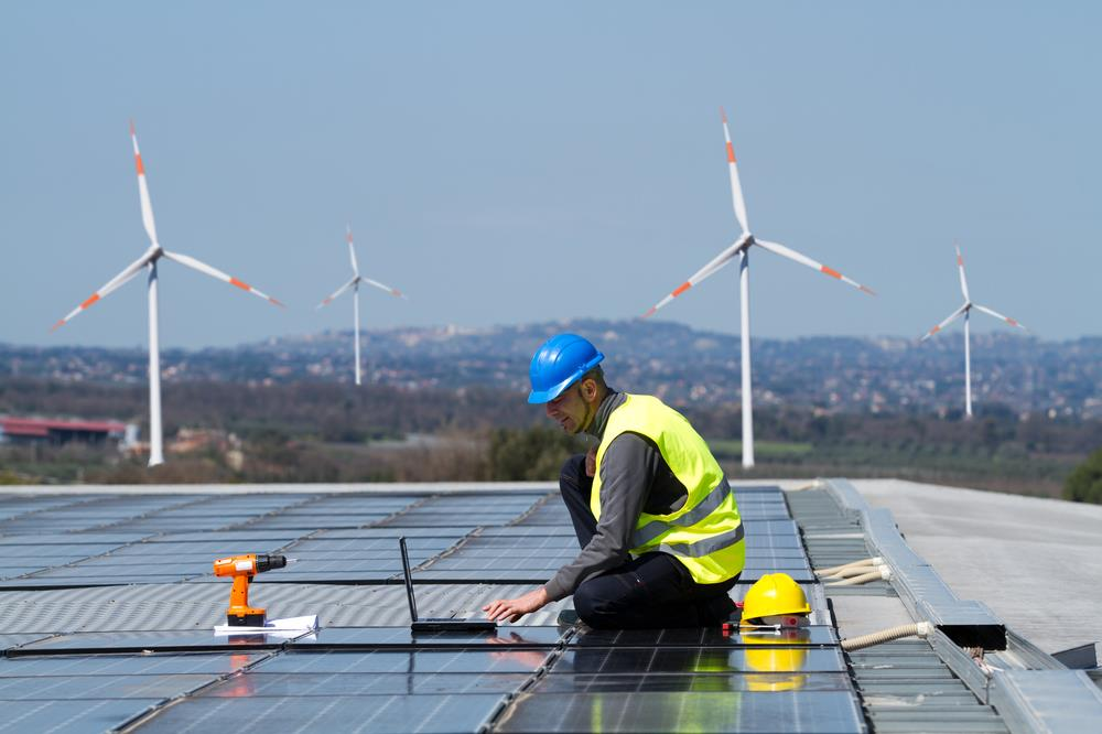 solar panel and wind turbine technician working on an installation project