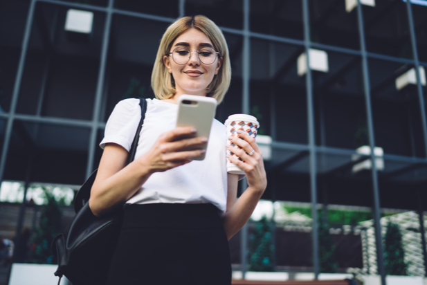 employee looking at phone and holding a cup of coffee