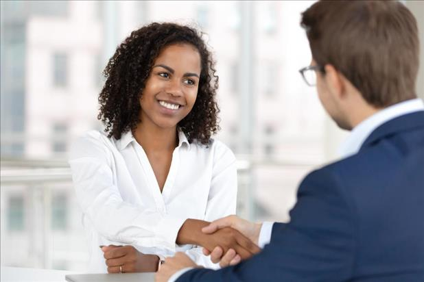 Candidate shaking hands with hiring manager after successful salary negotiation