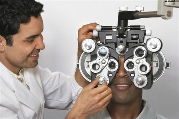 Optometrist performing an eye exam on a patient