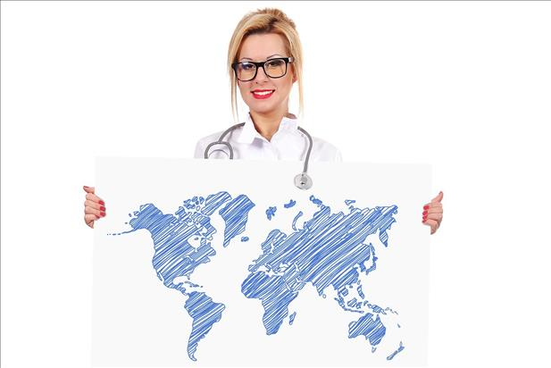 Traveling nurse holding up an illustrated map of the world