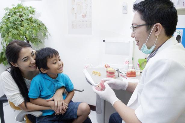 Community dental health coordinator educating mother and child on proper dental hygiene