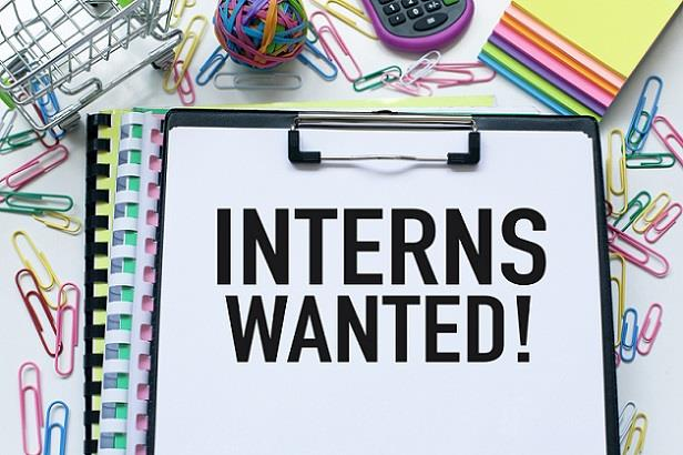 """Hiring manager's desk with flyer stating """"interns wanted!"""""""