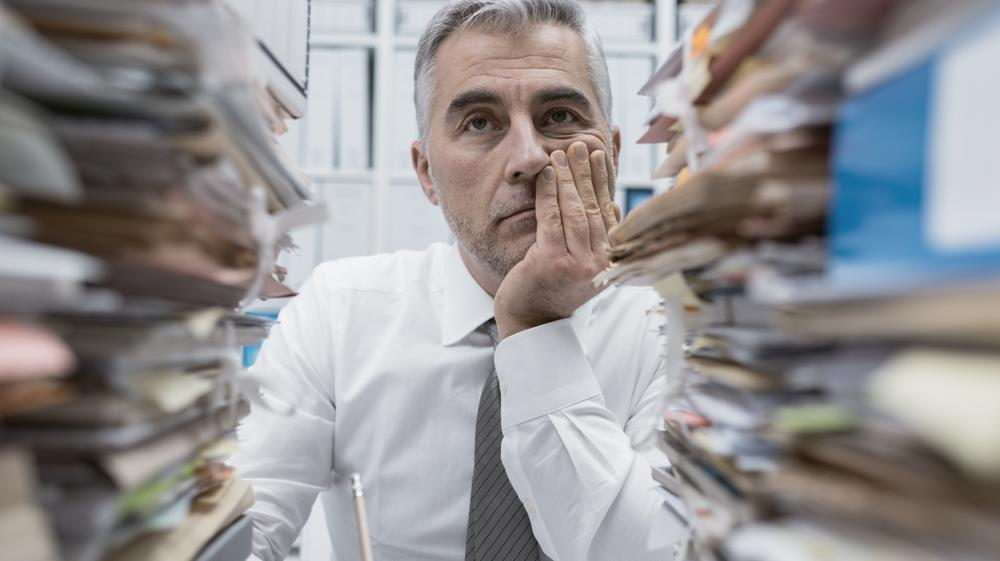Exhausted business man sitting among piles of work