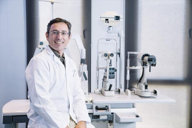 Ophthalmology physician assistant sitting in front of various equipment used in eye care