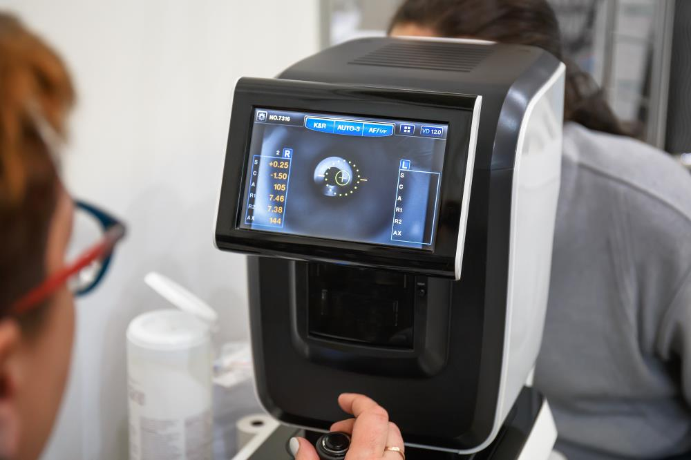 ophthalmic technician operating a diagnostic machine