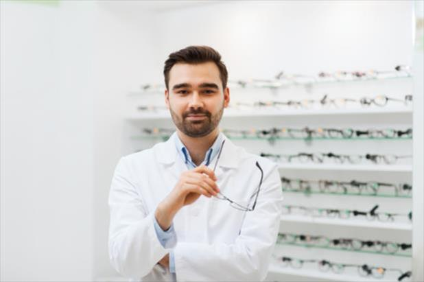 Optician standing in front of shelves with frames