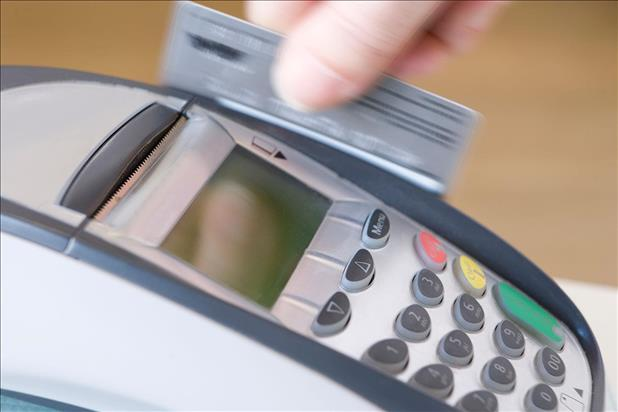 Credit card being swiped through a processing machine