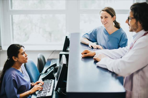 medical receptionist behind her desk looking up at two medical team members having a conversation