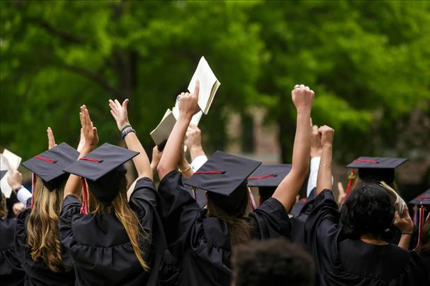 New college graduates in robes throwing their hands in the air