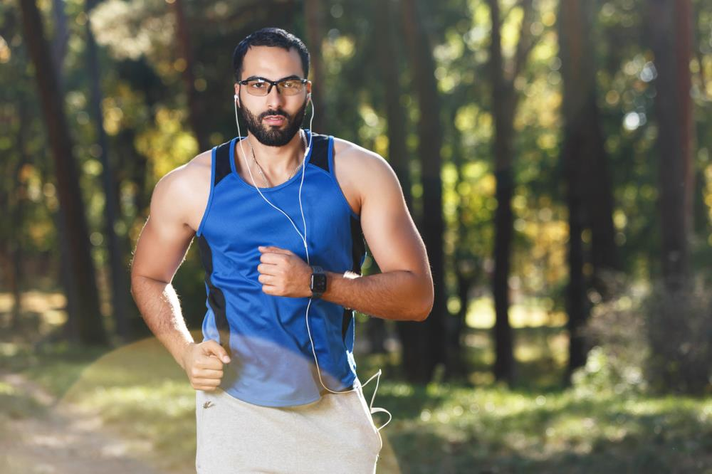 man running in the park with sports glasses on