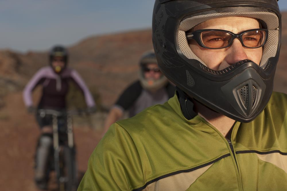 dirt bike rider with protective glasses on and fellow bikers in the background