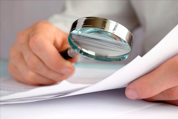 Hiring manager using a magnifying glass to examine a resume