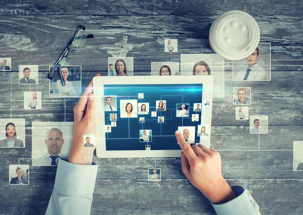 professional networking concept image with person on tablet and photos of people in their network