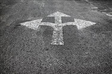 Asphalt with painted arrows pointing in three directions, representing the paths HR pros can take in their careers