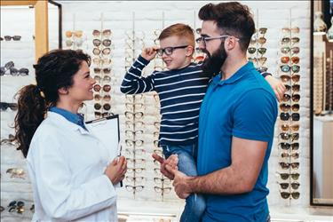 optometrist helping a father and son in her practice