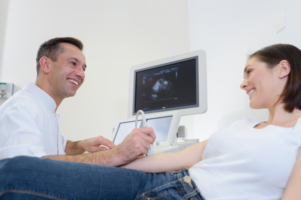 radiologic technologist performing a sonogram on a patient