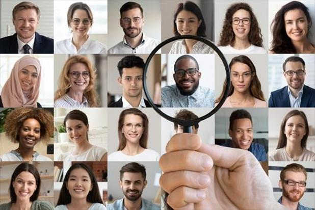 Recruiter holding up a magnifying glass to the right candidates amongst a panel of job seeker photos