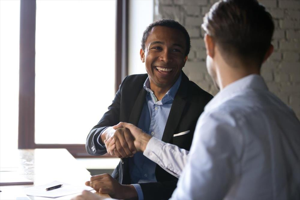 Man shaking hands with employer after negotiating job offer