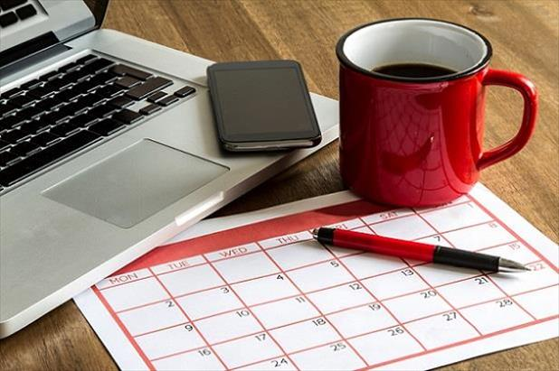 Laptop, phone, coffee cup, and calendar sitting on a desk