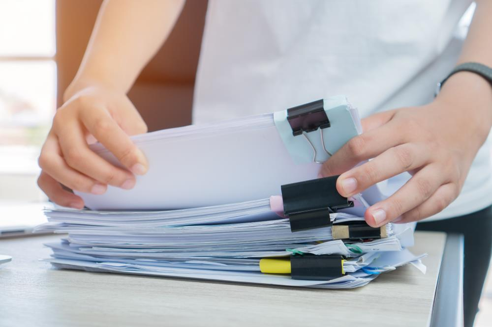 Woman looking through stack of paperwork