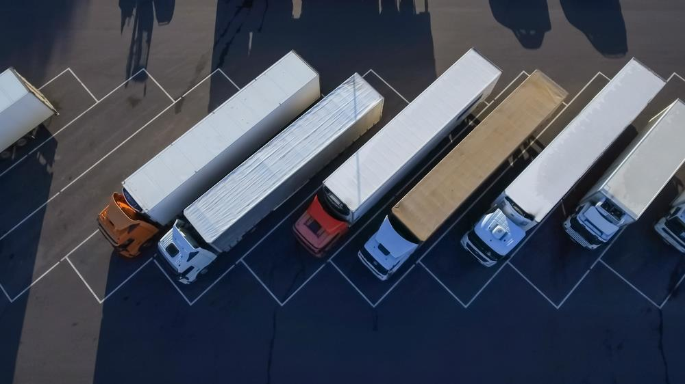 Birds-eye view of a group of semi trucks in a parking lot.