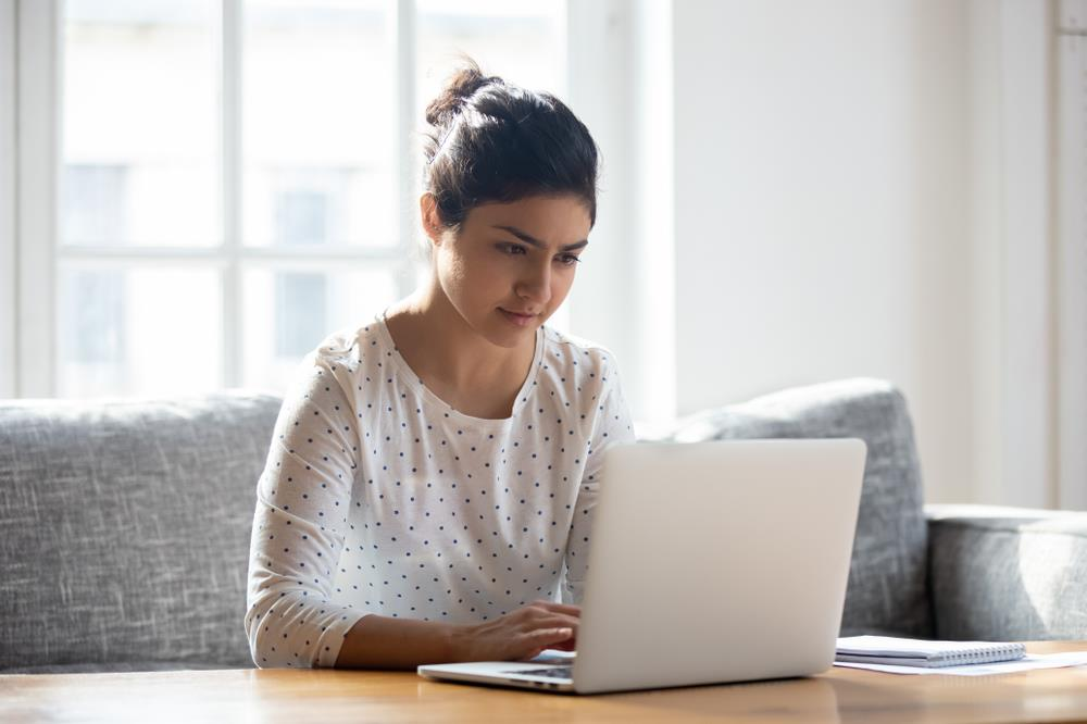 woman composing email on laptop at home