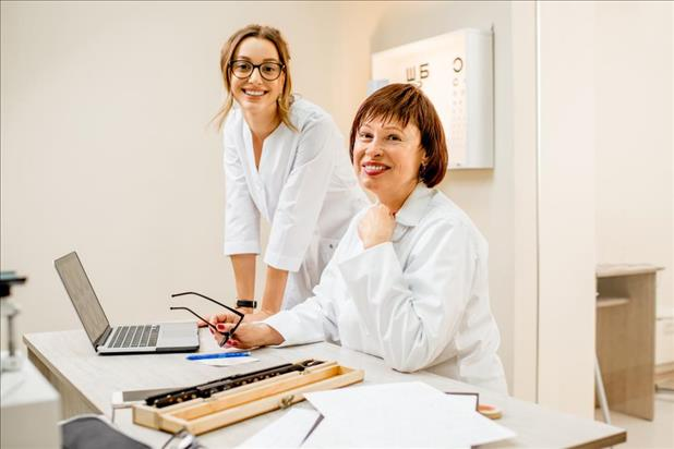 Smiling optometrist and optometric assistant posing inside their practice