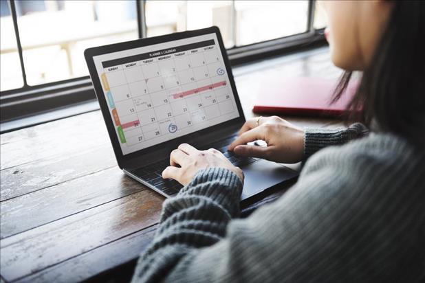 Job seeker reviewing schedule on laptop