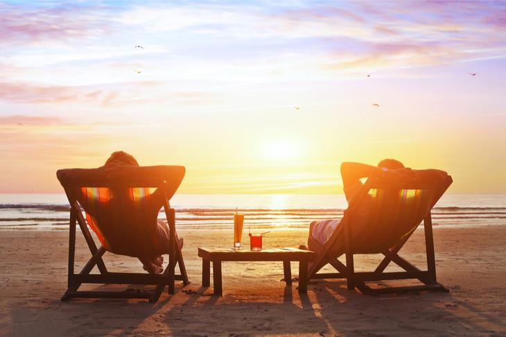 two people lounging on the beach