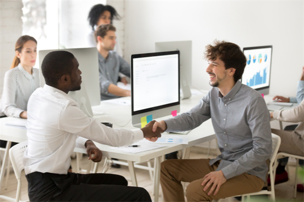 New hire shaking hands with coworker as part of onboarding process