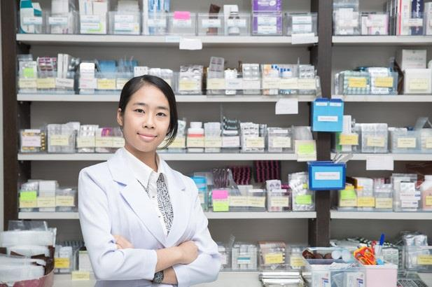 Pharmacist posing in front of shelves full of medications
