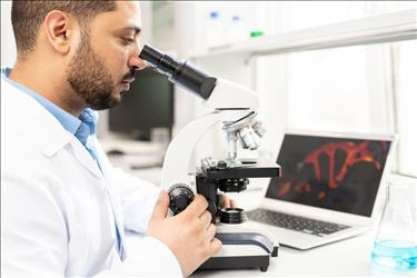 microbiologist studying a sample on a microscope