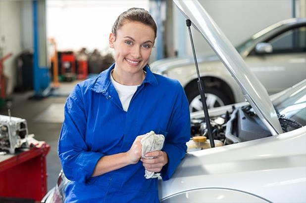 Woman mechanic leaning against car