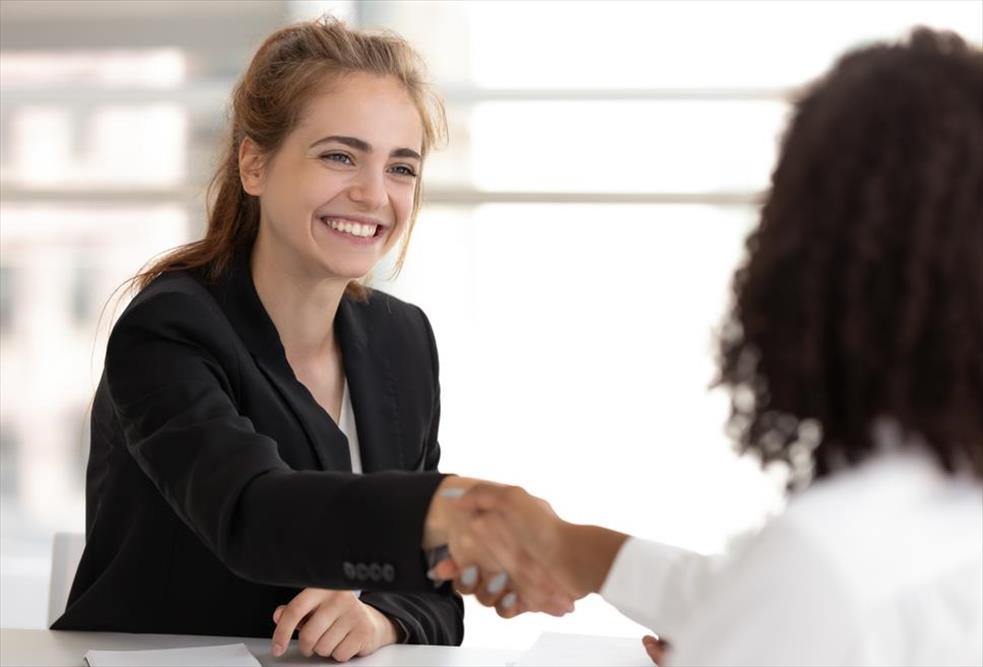 Jovial, blonde woman smiles and shakes hands with employer after accepting a job offer she earned thanks to her strong, authentic personal brand.
