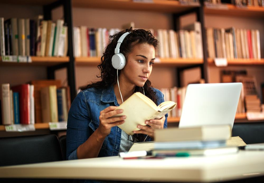 Job seeker wearing headphones sits in library, doing research on her computer as she embraces learning as the best pathway to growth and flexibility.