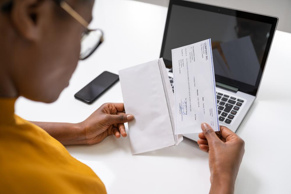 person putting a payroll check into an envelope