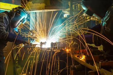 Two welders in steel fabrication facility