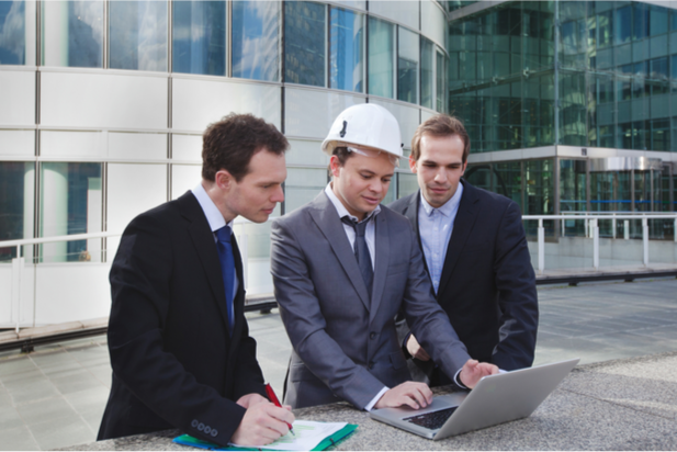 construction workers looking at laptop