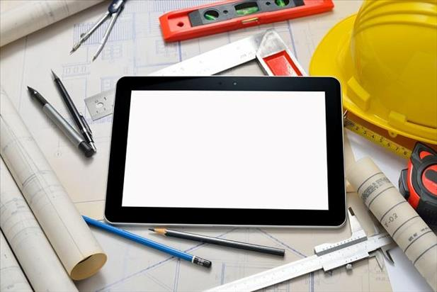 Blank tablet next to a hard hat and other construction-related materials