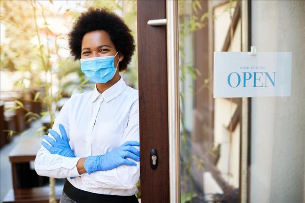 Business owner wearing mask proudly standing in front of her open restaurant