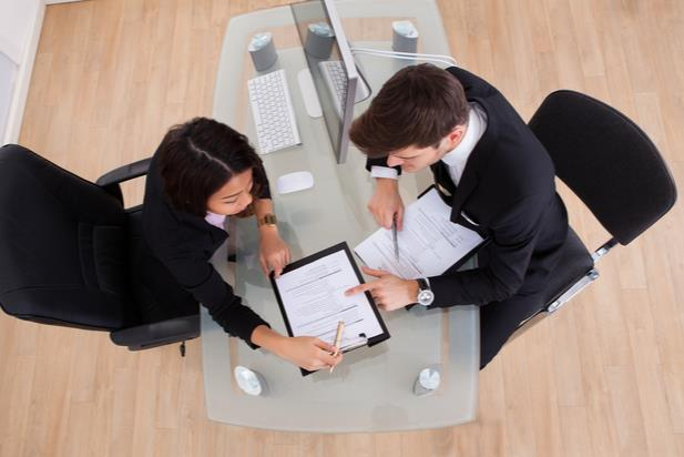 employees working at a desk looking at a document