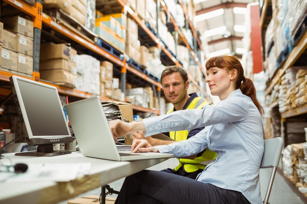 logistics business systems analyst reviewing data with a warehouse team member