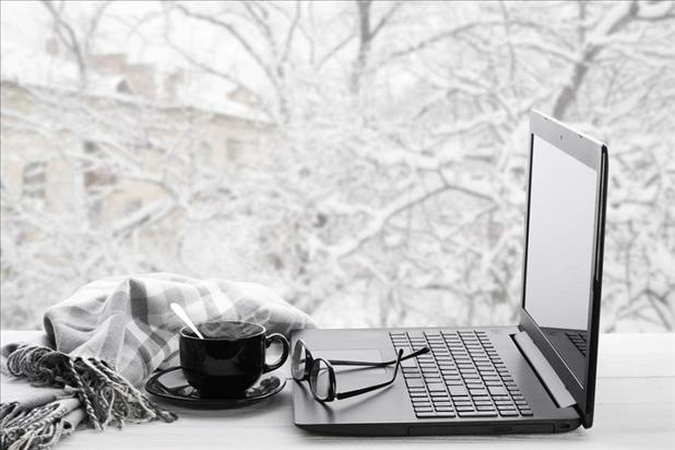computer on a desk with a snowy scene outside