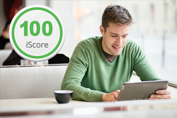 Man staring at laptop with iScore icon close by