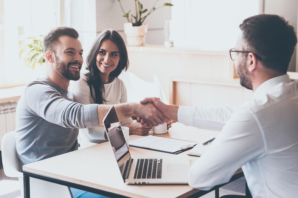 insurance agent shaking hands with a client after assisting a couple with their insurance needs