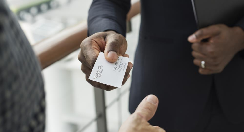 professional handing his business card to someone